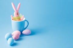 Süßigkeitsfarb-Ostereier mit Kaninchen über Minze Stockfotografie
