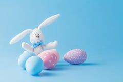 Süßigkeitsfarb-Ostereier mit Kaninchen über Minze Stockfotos