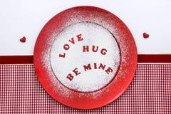 Süßigkeitsherzmitteilung auf roter Platte mit Süßigkeitenzucker Lizenzfreie Stockfotografie