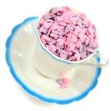 Süßigkeitsinnere in der Kaffeetasse über Weiß Stockfotos