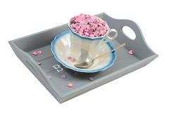 Süßigkeitsinnere in der Kaffeetasse auf grauem Tellersegment über Weiß Stockfotografie