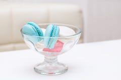 Süßigkeitsmakronen liegt in einem Glasvase für Bonbons auf einer weißen Tabelle Lizenzfreie Stockbilder