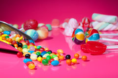 Süßigkeitzusammenstellung auf rosafarbenem Hintergrund Stockfotos