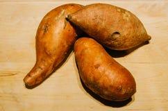 Süßkartoffeln auf hölzernem Hintergrund Lizenzfreie Stockbilder