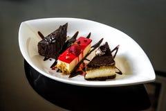 Süßspeise von Stücken Schokoladenkuchen und Käsekuchen mit Zuckerglasur und frischer Erdbeere Lizenzfreie Stockbilder