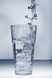 Süßwasser, das aus einem Glas heraus mit Eis spritzt Lizenzfreie Stockfotos