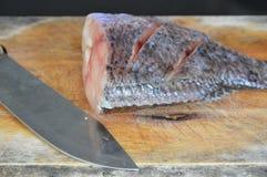Süßwasserfische und Messer bereiten sich für Koch auf hölzernem Hiebblock vor Stockfoto