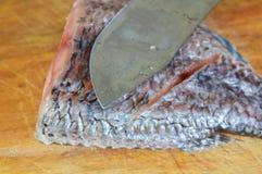 Süßwasserfische und Messer bereiten sich für Koch auf hölzernem Hiebblock vor Lizenzfreies Stockbild
