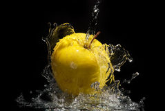 Süßwasserspritzen auf gelbem Apfel Lizenzfreie Stockfotos