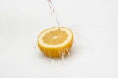 Süßwasserspritzen auf Hälfte der Zitrone. stockbild