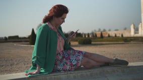 Süchtige junge Frau der Mode, die grüne gehobene genießende Sonne an einem Brunnen vor einem Palast trägt stock video