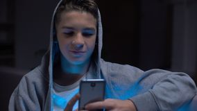 Süchtiger Jugendlicher des Geräts, der erwachsenen Inhalt auf dem Smartphone, Zeit vergeudend in einer Liste verzeichnet stock footage