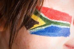 Südafrika-Markierungsfahne gemalt auf weiblicher Backe Lizenzfreies Stockfoto