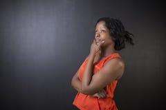 Südafrikanische oder Afroamerikanerlehrerin auf Kreideschwarz-Bretthintergrund Stockfoto