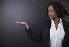 Südafrikanische oder Afroamerikanerlehrerin auf Kreideschwarz-Bretthintergrund Stockbild