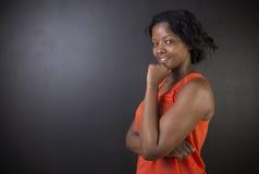 Südafrikanische oder Afroamerikanerlehrerin auf Kreideschwarz-Bretthintergrund Stockfotos