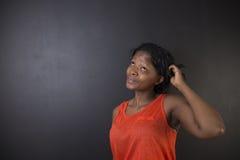 Südafrikanische oder Afroamerikanerlehrerin, die auf schwarzem Hintergrund denkt Lizenzfreie Stockfotografie