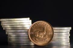 Südafrikanischer Goldmünze-Krügerrand vor Silbermünzen Stockbild