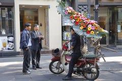 Südkoreanische Männer sprechen mit Mann auf dem Motorrad, das Blumen, Seoul Süd-Korea November 2013 liefert Lizenzfreies Stockbild