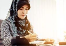Südostasiatische Islamfrau, die auf ein Buch schreibt lizenzfreie stockbilder