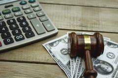 Sądzi młoteczek, kalkulatora i pieniądze na drewnianym stole, zdjęcia royalty free