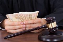 Sędziego odliczający pieniądze przy biurkiem Fotografia Royalty Free