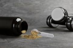 Słój i pomiarowa łyżka z konopianym proteina proszkiem, dumbbells i fotografia stock