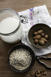 Słój owsa mleko z pucharami owsy i dokrętki Obrazy Stock