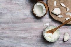 Słój z kokosowego oleju i dokrętki kawałkami fotografia stock