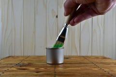 Słój z zieloną farbą i muśnięciem w ręce Zdjęcia Stock