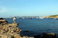 Sławna i turystyczna zatoczka Ibiza dzwonił Cala Bassa i kobieta na jej z powrotem stać na skale zdjęcie stock