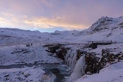 Sławna siklawa między zamarzniętymi skalistymi brzeg śnieżny mountai obrazy stock