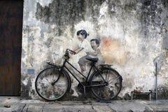 Sławni uliczni sztuki i graffiti obrazy dzieci Na bicyklu wzdłuż Armeńskiej ulicy, Penang, Malezja obrazy stock