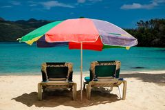 Słońc łóżka pod pastelem barwili parasol na karaibskiej plaży Obraz Royalty Free