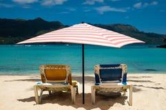 Słońc łóżka pod pastelem barwili parasol na karaibskiej plaży Fotografia Royalty Free
