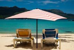 Słońc łóżka pod pastelu barwionym parasolem Obraz Royalty Free