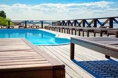 Słońc loungers basenem, ciepła lato pogoda, słoneczny dzień obrazy stock