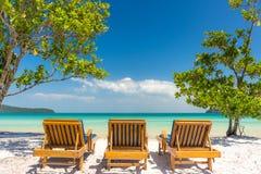 Słońc loungers na plażowy przyglądającym out raju morze Zdjęcie Royalty Free