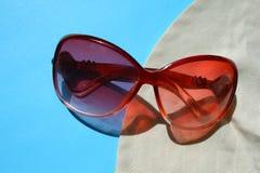 Słońc zbawczy szkła, kapelusz na błękitnym tle zdjęcie royalty free