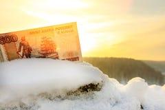 Słońca świecenie w niebie i rachunku Rosyjski rubel w śniegu obraz stock