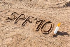 Słońca gacenia czynnik dziesięć SPF 10 słowo pisać na biel butelce z suntan śmietanką i piasku r obrazy stock