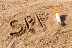 S?o?ca gacenia czynnik SPF s?owo pisa? na biel butelce z suntan ?mietank? i piasku r obraz stock