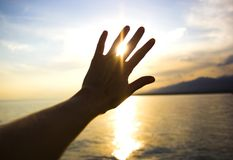 Słońca jaśnienie przez palców ręka na dennym tle Zdjęcia Stock