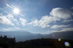 Słońca jaśnienie z kamera obiektywu racą nad halnym wierzchołka krajobrazem obraz stock