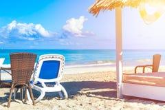 Słońca lounger blisko słomianego parasolowego łóżka na piaskowatej plaży niebem i morzem tła plażowy błękitny kolorowy nieba para fotografia stock