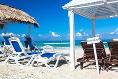 Słońca lounger blisko słomianego parasolowego łóżka z znakiem DLA czynszu na piaskowatej plaży niebem i morzem tła plażowy błękit zdjęcia stock