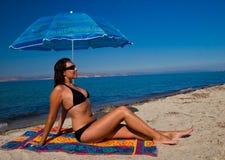 słońca na plaży parasol pod kobietami Zdjęcia Stock