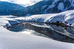 Słońce błyszczy w halnym jeziorze w śnieżystym krajobrazie w Gnade Alm, Austria obrazy stock
