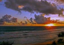 Słońce dotyka horyzont na tropikalnym wybrzeżu fotografia stock
