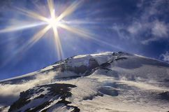 Słońce i sunbeams wysocy w niebie nad dużym lodowatym halnym szczytem obrazy royalty free